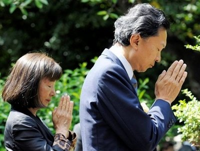 P.M. Hatoyama at the family grave, with his stellar companion and spouse (courtesy Yahoo)