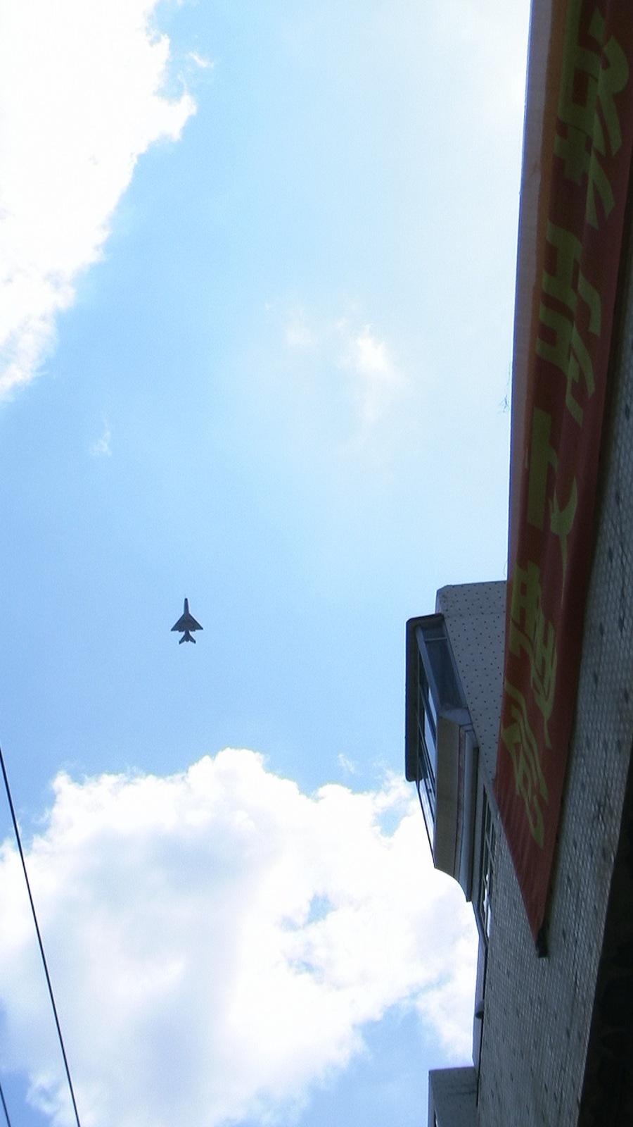 "Chinese Fighter Jet over Yanji (banner reads ""Establish a Civilized Yanji City,"" July 2009 -- photo by Adam Cathcart)"