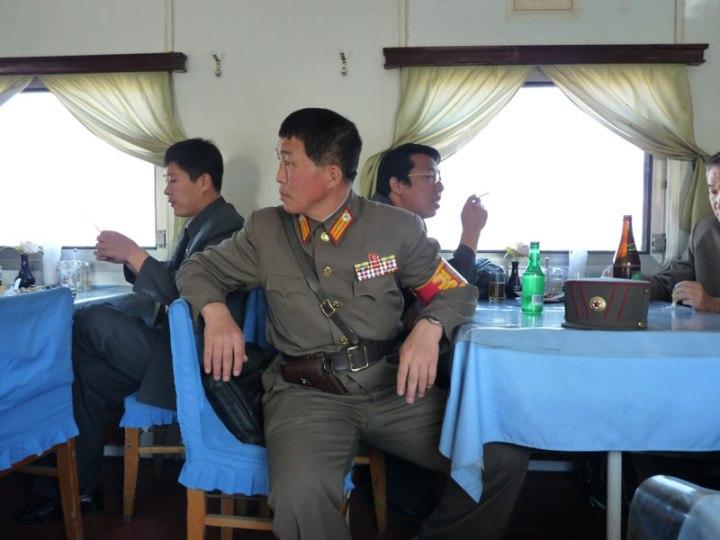 """On the 24-hour train from Pyongyang to Peking; """"Le retour à Pékin se fait en train. Un voyage de 24h auquel participe également un militaire nord-coréen.""""  Photo A. de la Grange, via Le Figaro"""